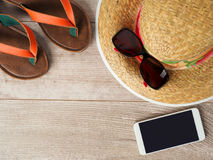 Straw hat, sunglasses, smartphone and slippers stock image