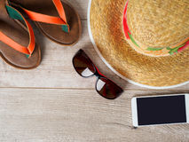 Straw hat, sunglasses, smartphone and slippers royalty free stock image