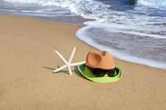Straw Hat, Sunglasses and  Starfish on the Empty Sea Beach Royalty Free Stock Photos