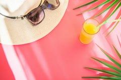 Straw Hat Sunglasses Tall Glass avec le fruit tropical Juice Palm Leaves d'agrume frais sur Cherry Pink Background Fuites de lumi photos stock