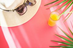 Straw Hat Sunglasses Tall Glass com fruto tropical Juice Palm Leaves do citrino fresco em Cherry Pink Background Escapes da luz s fotos de stock