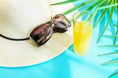 Straw Hat Sunglasses Tall Glass con la fruta tropical Juice Palm Leaves de la fruta cítrica fresca en fondo azul Escapes de la lu foto de archivo