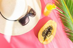 Straw Hat Sunglasses Tall Glass with Fresh Citrus Tropical Fruit Juice Papaya Palm Leaf on Pink Background. Sunlight Leaks Royalty Free Stock Photo