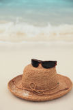 Straw hat and sunglasses on tropical island Royalty Free Stock Photos