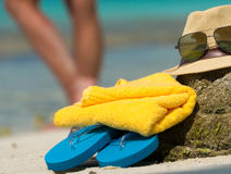 Straw hat, towel beach sun glasses and flip flops on a tropical Royalty Free Stock Images