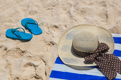 Straw hat, towel and flip flops on  sand beach Royalty Free Stock Photos