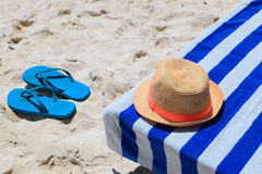 Straw hat, towel and flip flops on a tropical beach Stock Photo