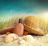 Straw hat with towel and lotion Royalty Free Stock Images