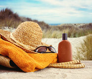 Straw hat with towel and lotion Stock Images
