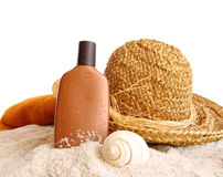 Straw hat with towel and suntan lotion on white stock photography