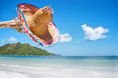 Straw hat on a tropical island. Beautiful tropical vacation in the warm sunny Seychelle island oceans and palm trees Royalty Free Stock Photo