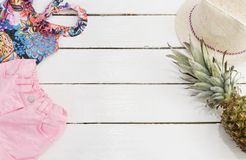 Straw Hat, Tropical Print Swimsuit, Pink Jeans Shorts, Pineapple. White Old Wooden Background royalty free stock photography