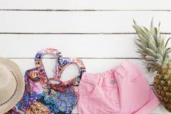 Straw Hat tropisk tryckbaddräkt, rosa jeanskortslutningar, ananas Vit gammal träbakgrund arkivbild