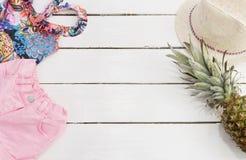 Straw Hat tropisk tryckbaddräkt, rosa jeanskortslutningar, ananas Vit gammal träbakgrund royaltyfri fotografi