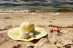 Straw hat and two red shells lie on the sand close up  a background of the sea Stock Image