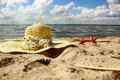 Straw hat and two red shells lie on the sand close up  a background of the sea Stock Photo