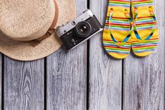 Straw hat, vintage photo camera and flip-flops. Top view, flat lay, summer, beach and travel concept. Wooden desk surface royalty free stock images