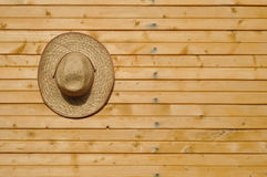 Straw hat on wall Stock Images