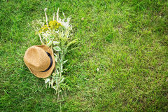 Straw hat and wild-flower bunch on green grass lawn Stock Photo