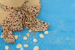 Straw hat for woman with leopard print, seashells on blue background. royalty free stock photos