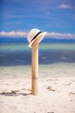 Straw hat at wooden fence on white sandy beach Royalty Free Stock Image