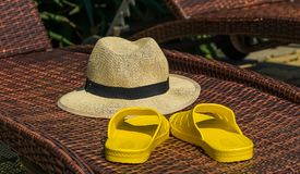 Straw hat and yellow flip-flops on a sunbed, by the pool at the stock images