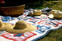 Straw Hats and Picnic Basket on Quilt. Old fashioned picnic scene with quilt and hats Stock Images