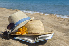 Straw hats, sunglasses and a book on the beach. Summer vacation Stock Photography
