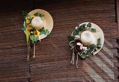 Straw hats on a straw wall. Two straw hats with floral decorations on a straw wall Stock Image