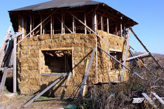 Straw house with a roof. Hexagonal house from straw bales with a roof Royalty Free Stock Images
