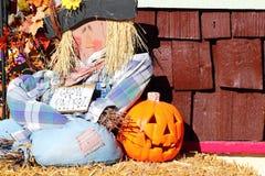 Straw man and jack o lantern. A straw man or scarecrow sitting on the ground beside a pumpkin or jack o' lantern Stock Photos