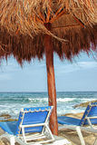 Straw palapa umbrella and lounge chairs overlooking the Caribbean Sea in Mexico. Straw palapa umbrella and two blue lounge chairs overlooking the Caribbean Sea Stock Photography
