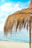 Straw parasol. With cloudscape and calm sea water on sand beach on a tropic island stock photography