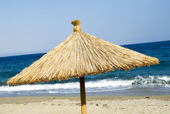 Straw parasol on the beach Stock Photography