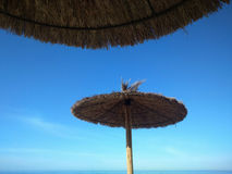 Straw parasol on beach Stock Images