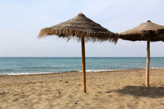 Straw parasols on beach Royalty Free Stock Images