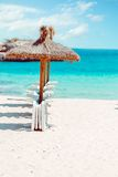 Straw parasols and beds on the sandy beach. Stock Image