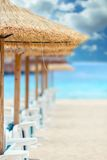 Straw parasols and beds on the sandy beach. Royalty Free Stock Images