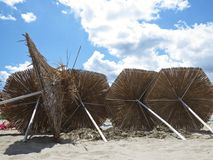 Straw Parasols Umbrellas Lying på Sandy Beach During Exotic Vacation royaltyfri foto