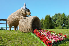 Straw pig sculpture and begonia flowers. Straw pig sculpture on meadow with blooming begonia flowers Royalty Free Stock Photography