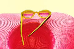 Straw Pink Beach Woman`s Hat Sun Glasses Top View. Pink Beach Woman`s Hat and Sunglasses Top View Yellow Background Flat Lay travel tour concept Copy space royalty free stock photography