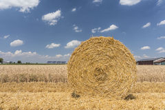 Straw roll bales with crop field, photovoltaic panel and blue sky in background Royalty Free Stock Photos
