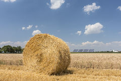 Straw roll bales with crop field, photovoltaic panel and blue sky in background Royalty Free Stock Image