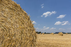 Straw roll bales detail with crop field, photovoltaic panel and blue sky in background Royalty Free Stock Photo