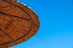 Straw roof of sun umbrella against the blue sky. Vacation topic.summer beach, background for an inscription.Texture of. Straw roof of sun umbrella against the stock photo