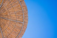 Straw roof of sun umbrella against the blue sky. Vacation topic.summer beach, background for an inscription.Texture of royalty free stock image
