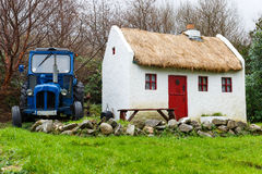 Straw roofed cottage and tractor Royalty Free Stock Photo