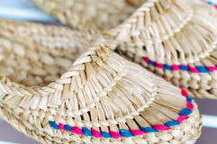 Straw shoes. A pair of woven straw slippers Stock Image