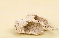 Straw shoes on yellow background. Straw baby shoes on a yellow background Royalty Free Stock Photo