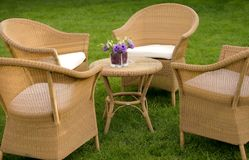 Straw sofas and table in garden Stock Image
